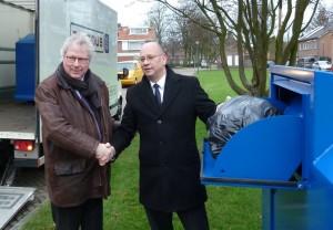 De eerste textielcontainer is geplaatst in Kaatsheuvel. Wethouder Gerard Bruijniks (rechts) werpt de eerste kleding in de container. Tegelijkertijd ontvangt hij de felicitaties van manager Pieter Springer.