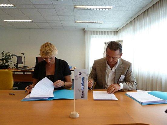 Marion van Limpt en Pasquale Cimmino zetten hun handtekening onder de samenwerkingsovereenkomst tussen Mondomed en Baanbrekers.