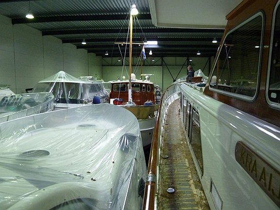 Een grote loods vol met boten die in onderhoud zijn bij Nautisch Centrum Heusden.