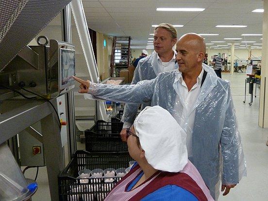 Onder het toeziend oog van Chris Velthoven jr. 'opent' wethouder Ronald Bakker de nieuwe vulmachine van Vero.