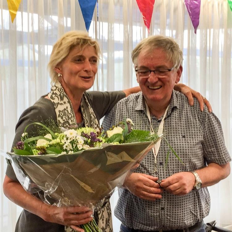 Gouden jubilaris Ad Fens ontving bloemen uit handen van Baanbrekersdirecteur Marion van Limpt.