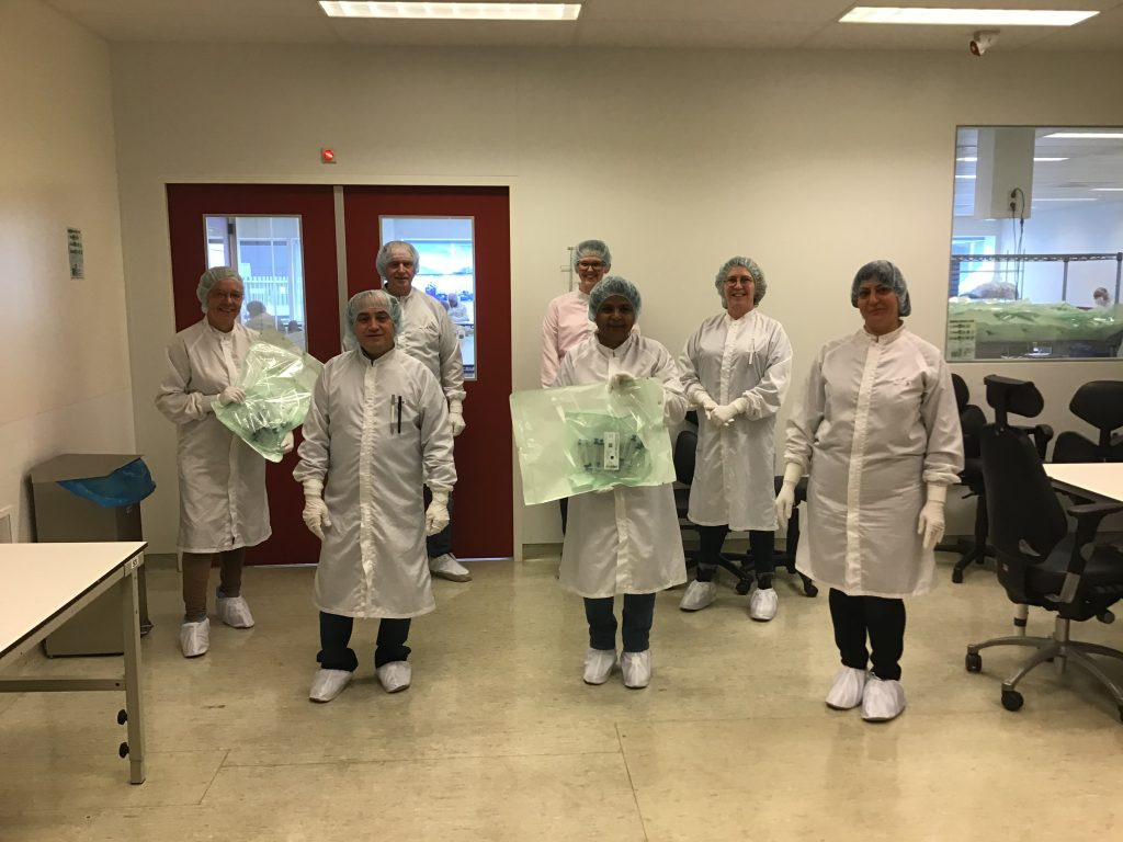 Een aantal medewerkers van de cleanroom samen met productmanager Jacqueline Wijsman (tweede van rechts) en afdelingsleider Arno Schapendonk (derde van links) in de voorruimte van de cleanroom.