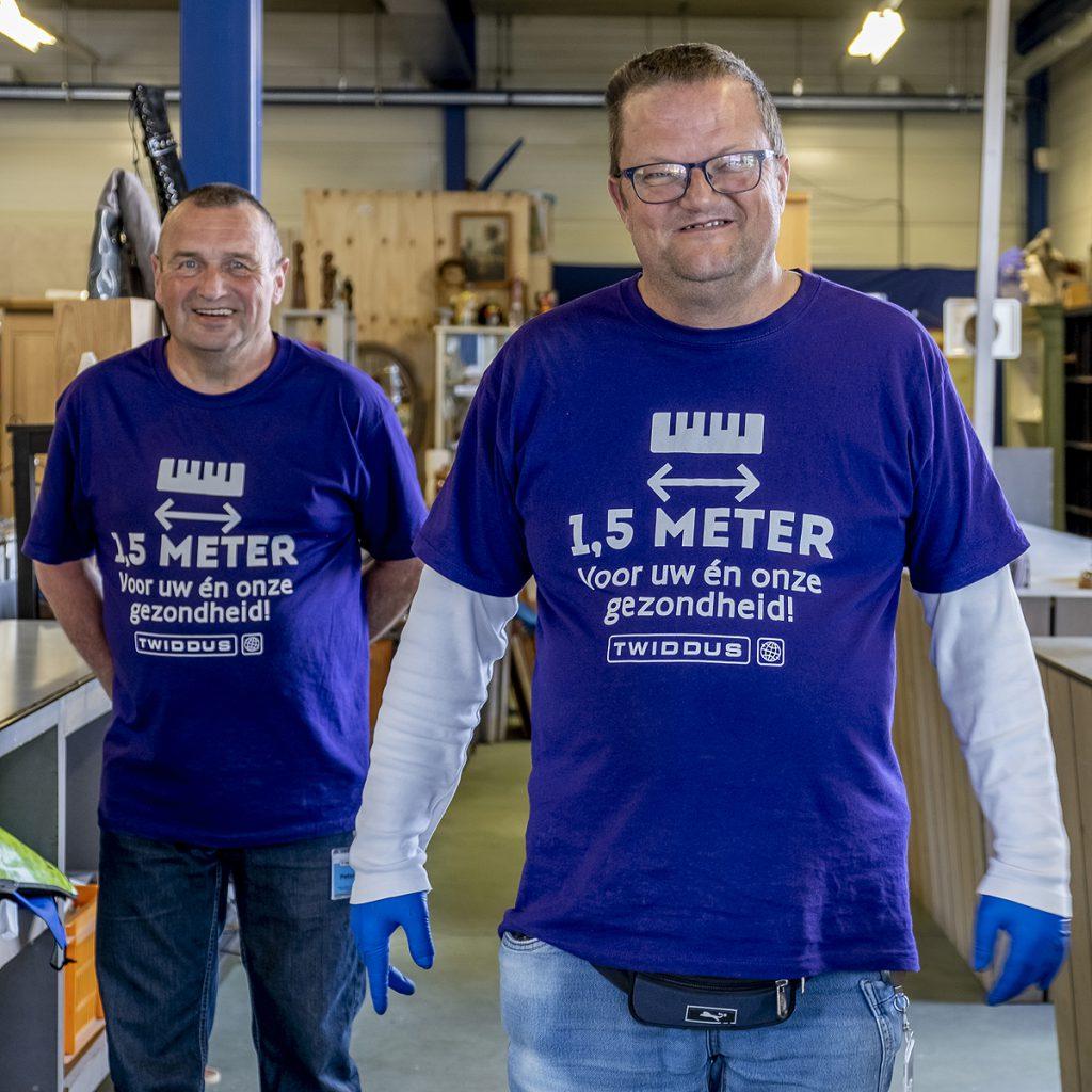 De winkelmedewerkers van Twiddus dragen tegenwoordig speciale coronashirts. Op de foto staan Peter Smeulders (links) en Adrie Kamp.